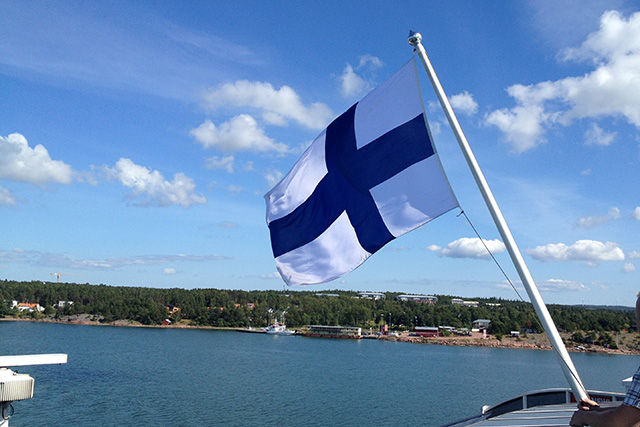 Finnish flag flying high above islands in the Gulf of Bothnia in the Baltic Sea.